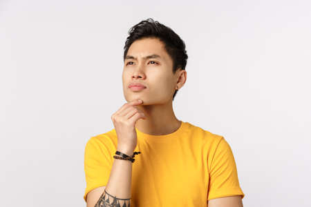 Thoughtful and smart, creative young asian man in yellow t-shirt, with tattoos, have deep thought, brainstorm, standing genius pose white background, touch temple and squinting, look aside Stockfoto
