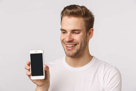 Joyful cute handsome blond bearded boyfriend in white t-shirt, holding smartphone, showing mobile display, smiling pleased, bragging with personal social media page, application score