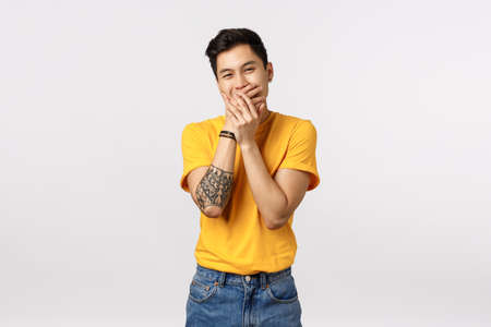 Silly and funny handsome asian young man, slip someone secret, giggle, smiling and cover mouth with palms, chuckling at important meeting, trying hold laugh, white background
