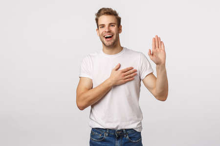 Man giving oath, swear telling truth or be honest. Happy confident and charismatic blond handsome man in white t-shirt, raise one hand and hold another on heart as making promise, white background