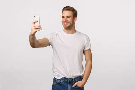 Say cheese. Friendly handsome smiling, stylish blond modern guy with bristle, extend hand holding smartphone, taking selfie and smiling, stream vlog online using mobile phone, white background Stock Photo