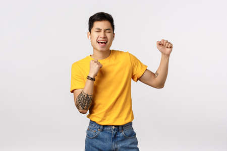 Guy sing with all his passion and soul, having fun, listening music in wireless earphones, close eyes singing along song, close eyes and relaxing, do karaoke, standing white background joyful