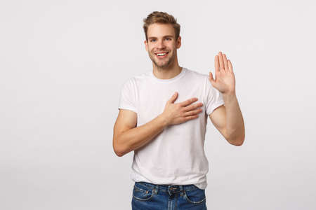 I promise you. Man giving oath with happy, relaxed smiling expression, hold hand on heart, raise arm as swearing, give wow, assure he telling truth, deserve trust, white background