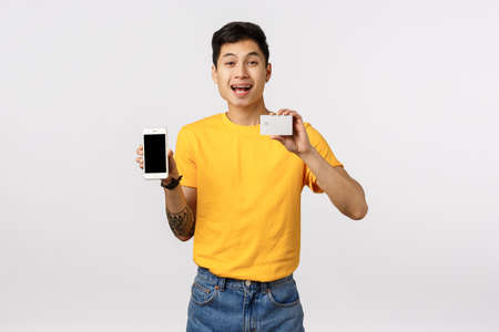 Happy smiling, cheerful asian guy in yellow t-shirt with tattoos, holding smartphone and credit card, recommend using online cashback, finance system, order product internet, white background