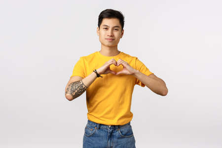 Love is in his heart. Cute and handsome young asian tattooed hipster guy in yellow t-shirt express affection making relationship symbol over chest and smiling with heartwarming grin, white background
