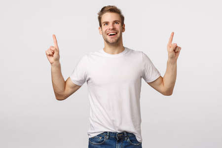 Impressed, carefree delighted, smiling young man feeling joy or happiness, grinning astounded or wondered, pointing looking dreamy up, watching amusing scene, standing white background charmed