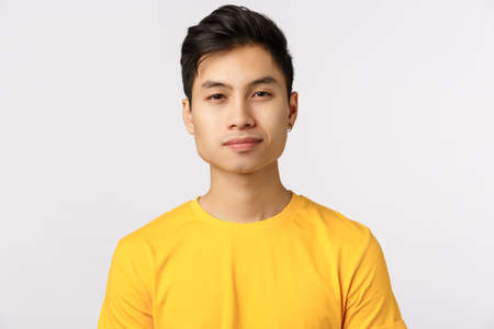 Close-up studio shot asian charming, modern hipster man in yellow t-shirt, smiling with confident, assertive expression, Newbie starting work in new company looking forward to meet coworkers Stockfoto