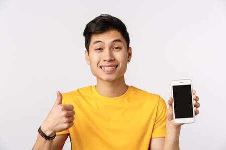 Close-up upbeat, friendly asian man in yellow t-shirt, show thumb-up in approval, like gesture, show smartphone display, promote online site, corporate banner or social page profile, white background