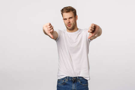 This movie sucks. Displeased and disappointed handsome blond guy give negative feedback, squinting from averstion, shake head in no, never, make thumbs-down gesture, standing white background