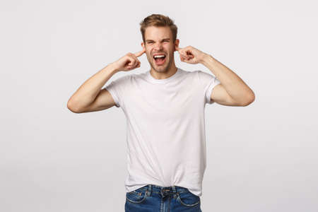 Angry annoyed and bothered blond guy shouting demand turn-off loud awful music, grimacing disturbed and pissed, shut ears with index fingers, complain on neighbours, asking silence
