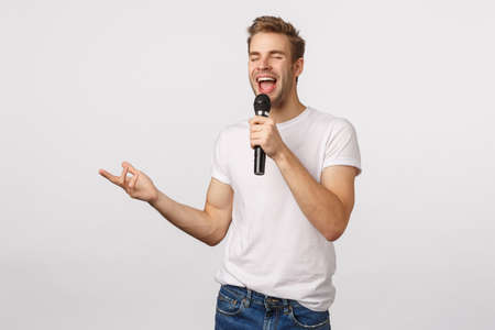 Carefree and joyful good-looking bearded blond guy in white t-shirt, holding microphone singing karaoke, gesturing, close eyes and smiling as feeling happy enjoy, standing white background Фото со стока