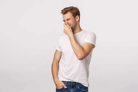 Gosh whats that smell. Disgusted and reluctant blond bachelor man open fridge and close nose with hand, squinting turn away from disgust, something reek, stink, standing white background