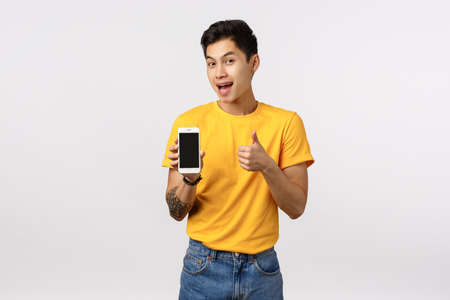 Attractive asian guy in yellow stylish t-shirt with tattoos, showing thumbs-up and smartphone display as offering customer download amazing app, editing application, game or corporate page