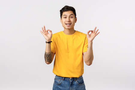 Guy trying calm down friend, telling all okay, everything fine. Happy and unbothered young asian man in yellow t-shirt, show ok, good or alright gesture, smiling rate excellent choice, leave feedback