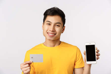Handsome and cute smiling asian man in yellow t-shirt, showing smartphone display and credit card, grinning delighted, recommend bank service, online paying system, standing white background