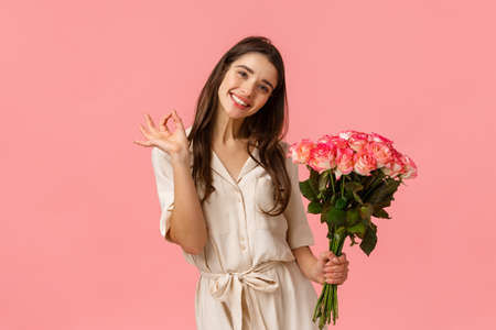 Lovely, dreamy and coquettish brunette female in dress, tilt head and smiling delighted, showing okay, good holding roses, got gift on valentines day, beautiful bouquet flowers, pink background