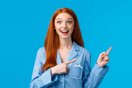 Excited girl hearing wonderful news, special discounts for holiday season. Attractive redhead female teenager nightwear smiling astonished and delighted, pointing upper right corner, blue background Stock Photo