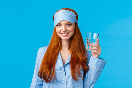 Waist-up shot glamour redhead woman taking care health, eating healthy, drinking water, wearing sleep mask and nightwear, holding glass and smiling energized, standing blue background