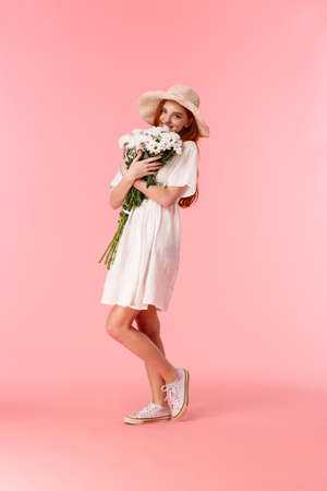 Full-length vertical shot lovely, romantic and happy redhead girlfriend in straw hat, cute dress, hugging big beautiful bouquet, smelling flowers and smiling, blushing from receiving gift Reklamní fotografie