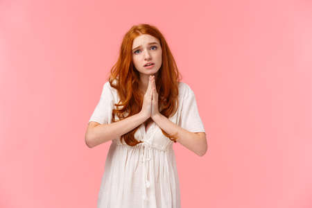 Pleading cute and silly redhead girl acting innocent, press hands together in pray, asking for favour, hopefully looking at camera, frowning gloomy, need something, begging over pink background Foto de archivo