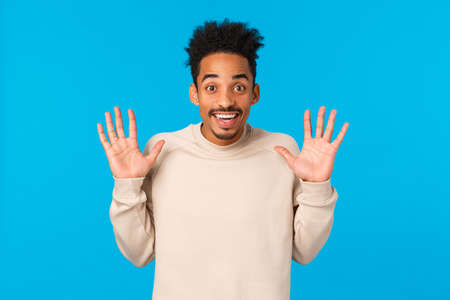 Hey no hands, I got nothing. Cheerful smiling handsome african american boyfriend fooling around, raising palms in surrender gesture, joking express positive emotions, winter concept, blue background