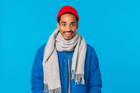 Amused and excited smiling young handsome african-american hipster guy in trendy red beanie, scarf and winter padded jacket, grinning astonished and curious, standing blue background