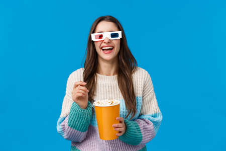Girl watching comedy in cinema. Carefree happy young brunette woman in winter sweater, enjoying funny movie, laughing out loud eating popcorn, wearing 3d glasses, standing blue background Stock Photo