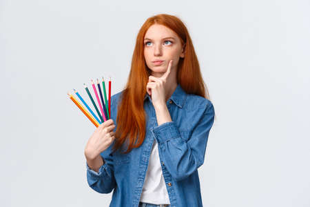Thoughtful and focused, serious-looking determined redhead female student, teenager want draw something interesting, holding colored pencils look up thinking, pondering ideas
