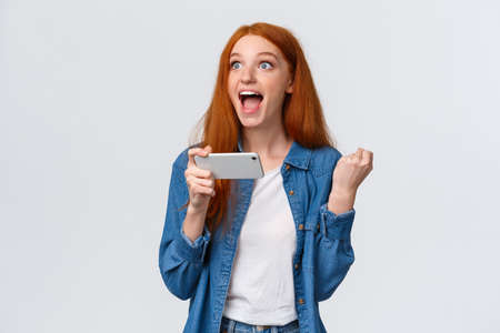 Happy astonished redhead girl cant believe she just won, feeling lucky and satisfied, fist pump, holding mobile horizontally, playing smartphone game, yelling yes, hooray over white background