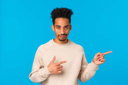 So lame, gosh. African-american good-looking man with moustache, afro haircut smirk skeptical looking with sarcastic expression, pointing right unsatisfied and unimpressed, blue background