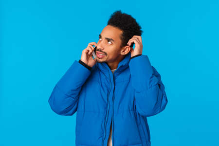 Perplexed and indecisive young man cant recall info, don't know answer, hesitating what say as talking on phone, scathing head doubtful looking away and holding smartphone near ear, blue background