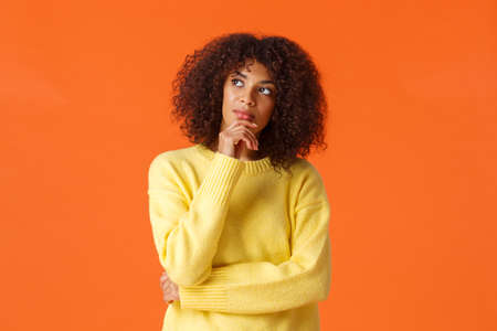 Waist-up portrait unsure, thoughtful young creative african-american female entrepreneur making new ideas, standing orange background, searching inspiration, thinking looking up