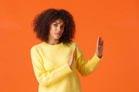 I said no. Serious-looking assertive and determined african-american woman looking camera and make stop, refusal gesture to right side, decline offer, feel reluctant, standing orange background Archivio Fotografico