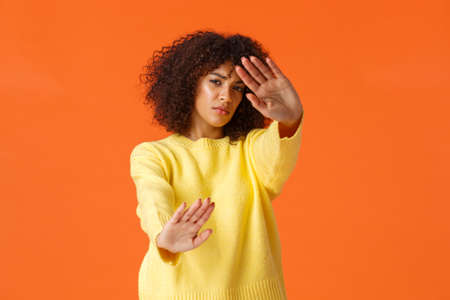 No stop, turn-off lights. Displeased grumpy cute african-american woman with afro haircut cover face from spotlight, defending from glimmering light, standing orange background reluctant