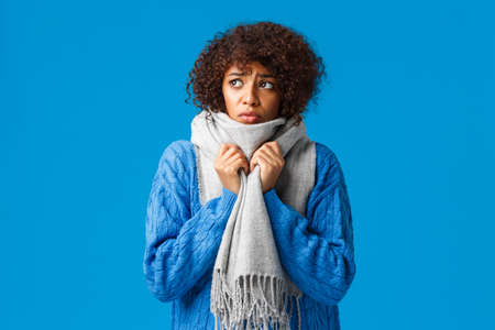 Silly and sad, gloomy african-american girl looking outside windy snowy weather winter, wrap neck with warm scarf, tremble from cold feeling discomfort from low tempreture at home, blue background 版權商用圖片