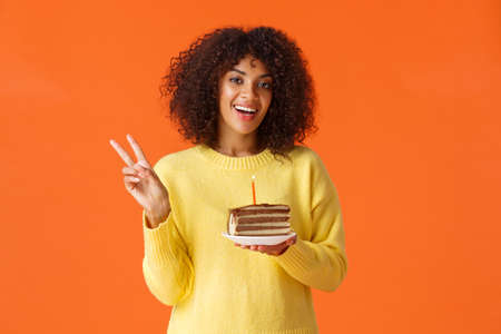 Waist-up portrait happy african-american woman in yellow sweater, showing peace sign and say cheese, birthday girl taking photo with b-day cake and candle, making wish, standing orange background