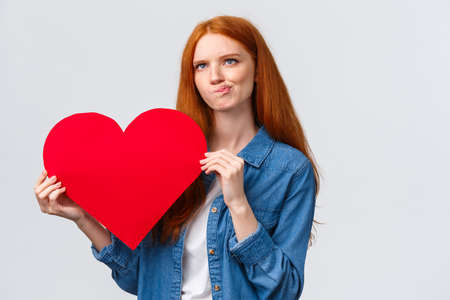 Thoughtful and focused, serious-looking redhead girl trying think, smirk indecisive and unsure, looking up pondering, holding big red valentines day heart, white background Banco de Imagens