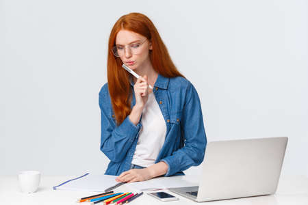 Serious looking focused and determined redhead female working over important project, design for company, work freelance, thinking, pondering as writing, stand near laptop and colored pencils