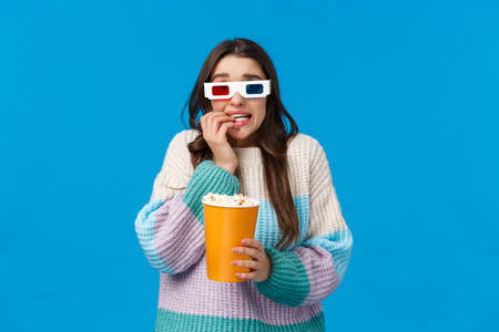 Waist-up portrait astonished and scared young brunette girl in winter sweater, watchign scary movie, premiere in cinema, wear 3d glasses, biting fingernails and holding popcorn, afraid of film scene