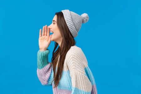 Vienes o no. Chica morena sonriente saliente feliz y despreocupada en suéter de invierno de moda, sombrero, gire a la izquierda y sosteniendo la mano cerca de la boca abierta, llamando a alguien, buscando amigo en la multitud Foto de archivo