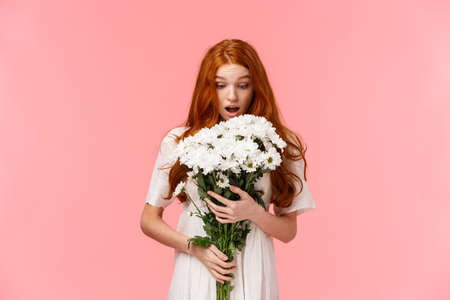 Surprised attractive redhead girl receive romantic valentines day gift, looking at beautiful bouquet of flowers amazed and wondered who might sender be, standing over pink background