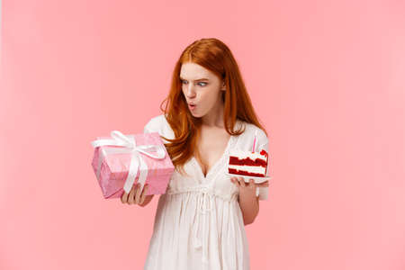 Amazed, fascinated good-looking redhead teenage girl celebrating birthday, astonished with amount of surpirses, holding peace birthday cake with candle, looking impressed at gift