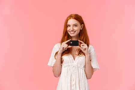 Time to use my secret weapon. Silly and cheerful assertive redhead girl going shopping, holding her credit card and smiling mysteriously, have in mind how waste all money on bank account