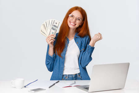 Girl sold her program, freelancer got payed for project, design standing white background cheerful, shaking fists triumphing, celebrating big money, won prize, holding cash dollars Фото со стока - 137770576