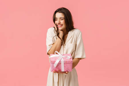 Anticipation, celebration and party concept. Cheerful lovely young woman in dress, cheering close eyes happily smiling and laughing, receiving nice present, got pretty gift, pink background