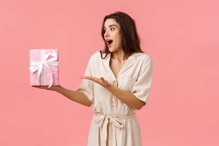Girl likes surprises. Amused and happy cheerful young brunette woman in dress, receive gift box, pointing at present looking impressed and astonished as didnt expect such cuteness, pink background