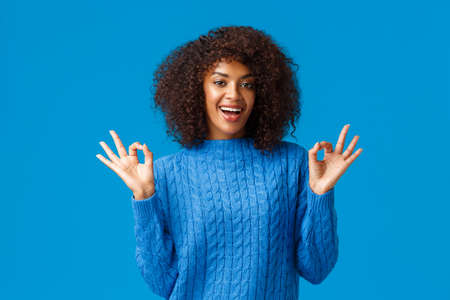 Alright it was awesome. Cheerful african-american woman having fun, rate good movie, give recommendation, smiling in approval, showing okay, good ok gesture and standing blue background
