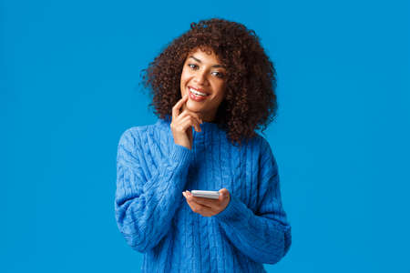 Hmm interesting. Intrigued and dreamy, creative african-american girl think-up christmas congratulation message, holding smartphone smiling and touching lip thoughtful, pondering, blue background
