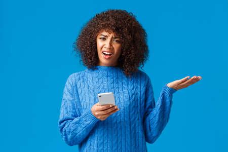 Wtf en cours, quelqu'un m'explique. Une femme afro-américaine gênée et confuse en pull d'hiver, haussant les épaules, lève la main avec consternation, l'air interrogé et énervé, tenant un smartphone