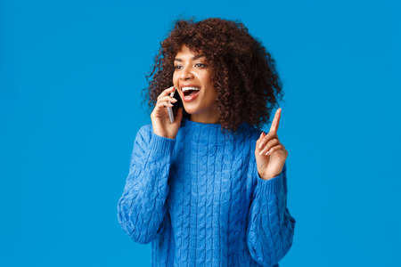 Girl remember something and telling it friend as raising index finger in eureka gesture and smiling, found answer, suggest something useful for friend, standing blue background joyful